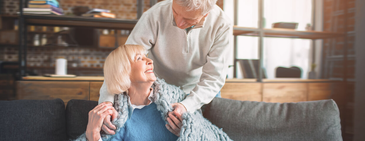 Portrait of senior couple, man putting a blanket on woman or wife while she sits on the couch, caring for a loved one concept after heart surgery during recovery