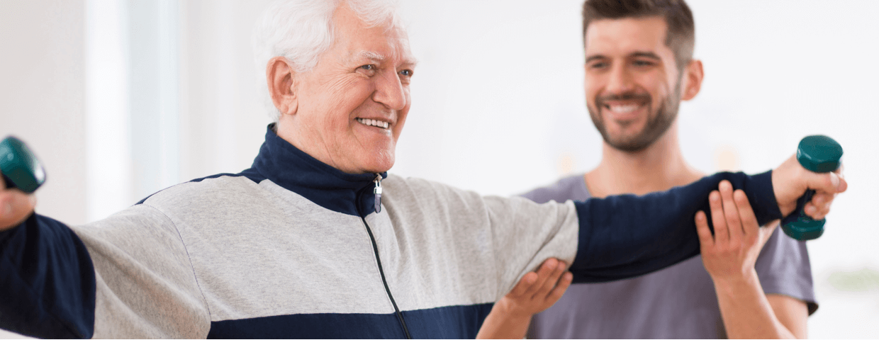 senior man doing physical therapy or cardiac rehab with a trainer after heart surgery
