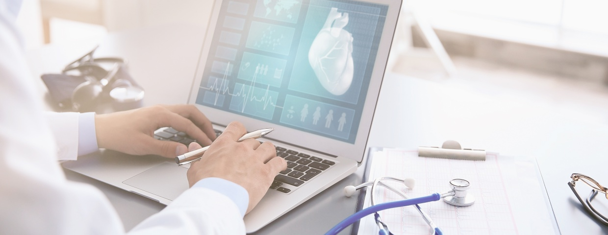 cardiologist looking at heart on laptop