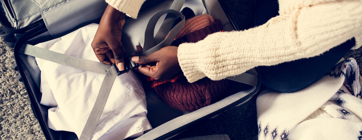 closeup of woman's hands clipping the straps of a packed suitcase, packing concept
